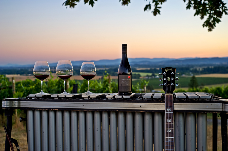 Bottle of Carlton Cellars Estate Pinot Noir and three wine glasses on vibes at sunset and gibson guitar