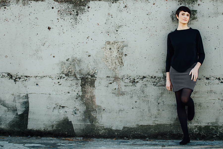 Many Weathers grey fleece skirt worn by a woman leaning against a cement wall.