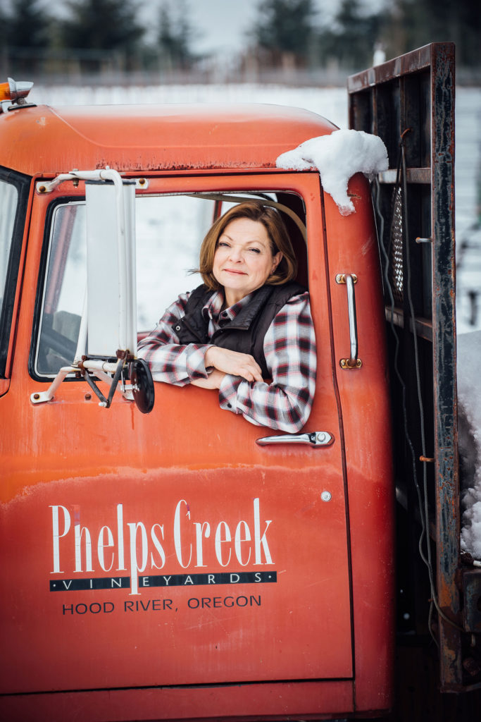 Lynette Barss Morus general manager inside vintage red  International flatbed on a snowy afternoon in the vineyard at Phelps Creek Vineyards in Hood River, Oregon