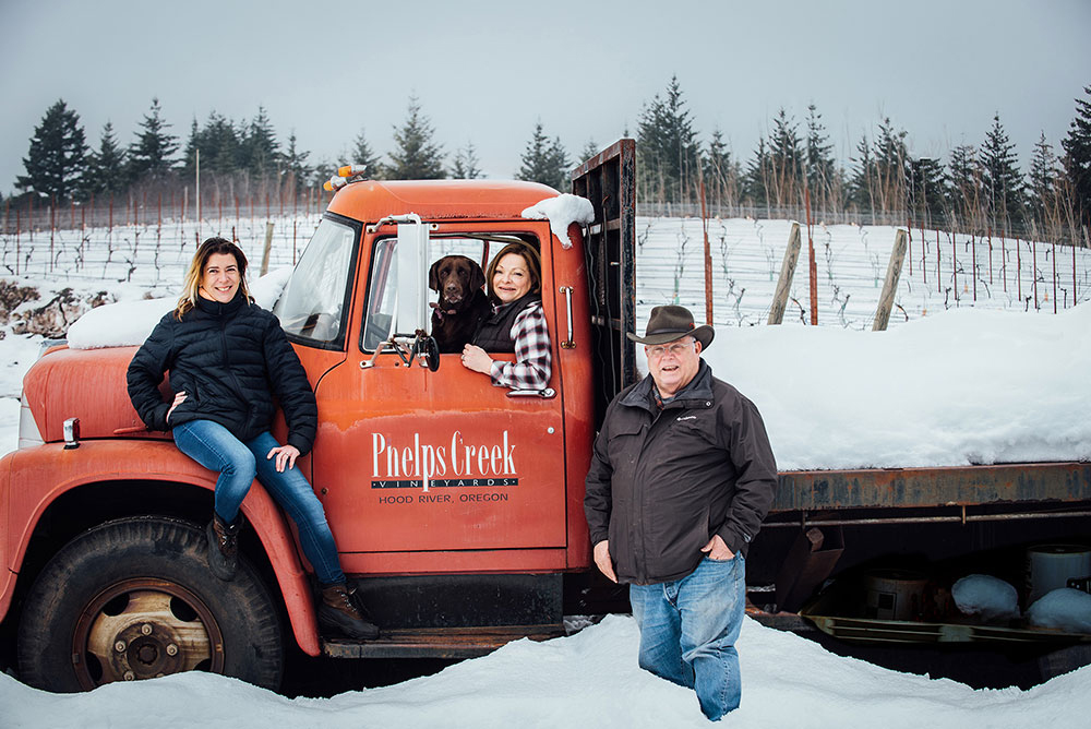 Winemaker Alexandrine Roy, Rosie, founders of Phelps Creek Vineyards, Lynette Barss-Morus and Bob Morus with their red vintage International Flatbed truck on a snowy afternoon at the winery.